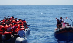 Moas rescuers throw bottles of water to refugees in a rubber raft near Malta in August 2014.