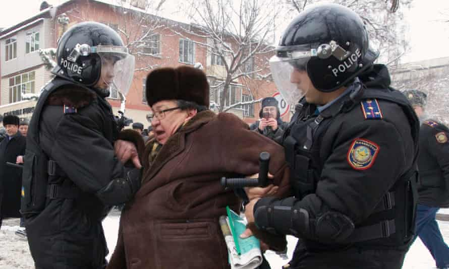 Riot police detain an opposition supporter after protesting against the government's actions during the Zhanaozen clashes.