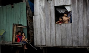 """In this April 19, 2015 photo, children fish from their home sitting just above the water line in the Belen neighborhood of Iquitos, a community in Peru's Amazon nicknamed """"Venice of the Jungle."""""""