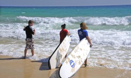 Two girls take their first surfing lesson Rainbow Beach, Queensland.