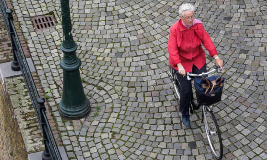 An old lady riding a bicycle.