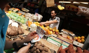 A man at a greengrocer pays with Brixton pounds