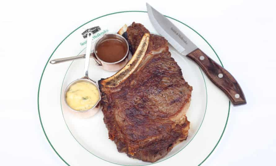 Smith & Wollensky's bone-in ribeye steak next to sauces in pots and a knife
