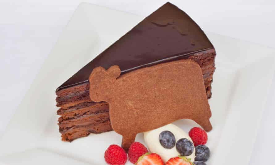 Slice of rich layered chocolate cake next to a cow-shaped biscuit, some cream and raspberries, blueberries, strawberries