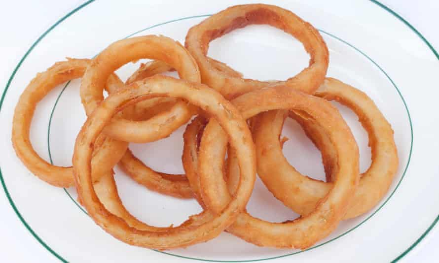 10 battered onion rings overlapping on a plate