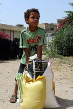 A Yemeni boy receives food aid
