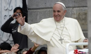 Pope Francis waves as he rides in the popemobile through the Ecuadorean capital, Quito.