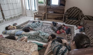 Children lying on a large rug on the floor, some with a blanket over them, at Hope VIllage