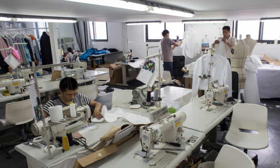 A man at a sewing machine and others working in Masha Ma's Shanghai studio.