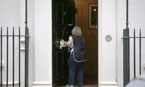 Cleaner polishes door of 11 Downing Street