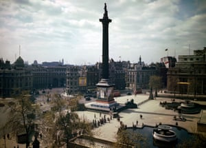 A view of Trafalgar Square in London showing 'Carry on London' and 'Salute the Soldier' propaganda hoardings on Nelson's Column