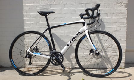 The Trek Domane 4.0 Disc relaxing by a wall.