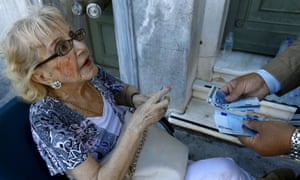 A woman receives her pension outside a bank in Athens.