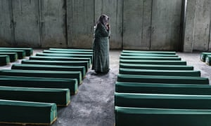 A Bosnian women mourns by a coffin of he