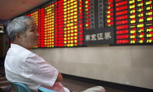 An investor looks at an electronic board showing stock information at a brokerage house in Nanjing