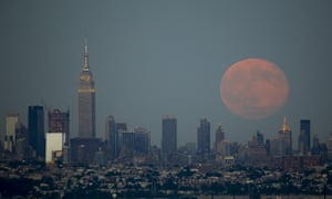 The blue moon rises next to the Empire State Building and middle Manhattan in New York City, US.
