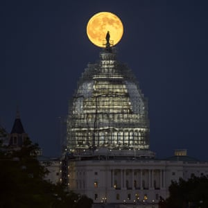 The second full moon for the month of July rises behind the dome of the U.S. Capitol in Washington, DC.
