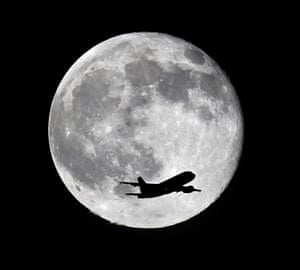 An American Airlines passenger airplane from Miami crosses a blue moon over Whittier, Calif., as it heads to Los Angeles Airport.