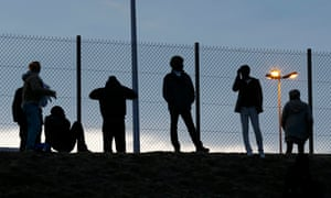 Migrants gaze through a fence near the Channel Tunnel access.