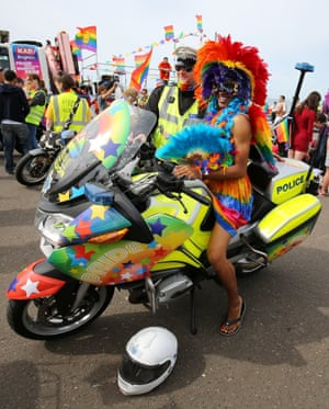 A Pride-goer sits on the bike of a very happy policeman