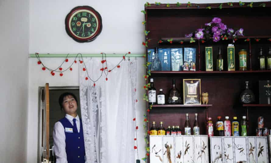 A waitress under a clock in Rason city, North Korea. On 7 August, Pyongyang announced a new time zone for the country – a move that South Koreans have blasted as 'regrettable'.