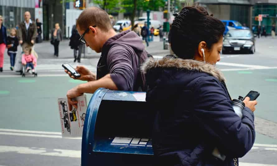 Two people leaning on mail box while using iPhones near Columbus Circle, New York City.
