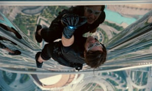 In a still photo from the film Mission Impossible: Ghost Protocol, Tom Cruise climbs the outside of the Burj Khalifa Tower in Dubai as we look down from above him to the ground far below.