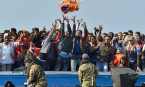 Royal Marines with migrants rescued off the Libyan coast in June.