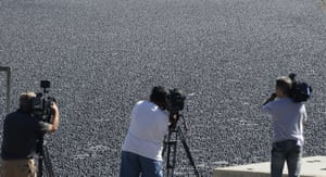 Photographers in front of LA reservoir full of black balls