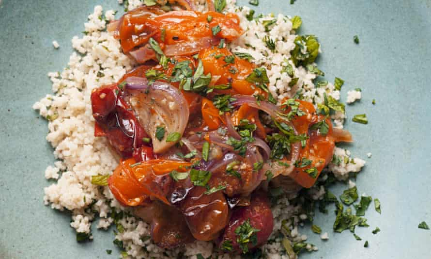 A mound of roast tomatoes with mint and parsley couscous on a plate