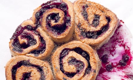 Five blackcurrant and poppy seed buns attached in a spiral with jam smeared on the side