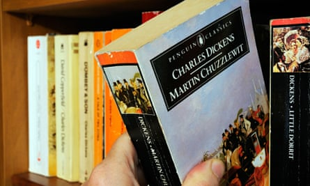 A hand taking Charles Dickens's Martin Chuzzlewit from a bookshelf