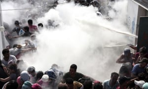 Police on Tuesday tried to disperse hundreds of migrants by spraying them with fire extinguishers during registration in the stadium.