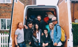 The team of young people pose in front of a van