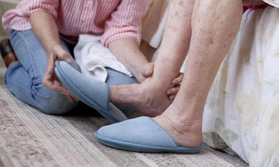 A woman helping an elderly woman put on slippers