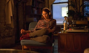 Lola Kirke as Tracy sits on an upholstered chair with her legs tucked up and to the side, in the warm glow of a lamp as she listens on headphones to a record playing on the turntable.