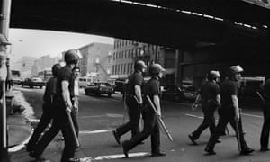 Riot police cross a street in 80s New York