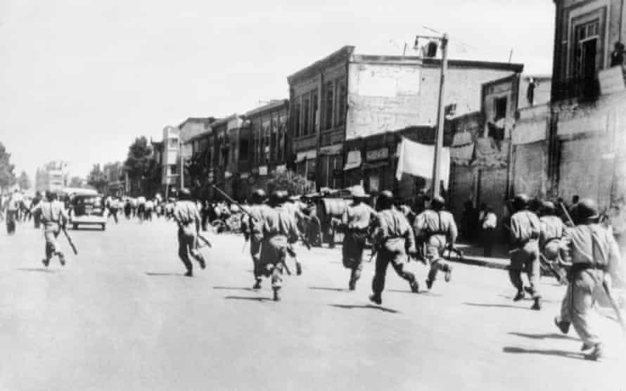 Iranian soldiers chase rioters during civil unrest in Tehran in August 1953.