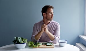 ed smith sits at a table with a chopping board of fresh greens in front of him