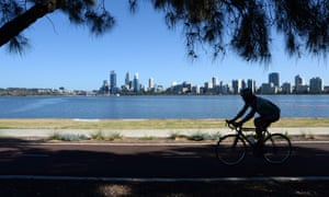 A cyclist rides along the Swan River in Perth, Australia.
