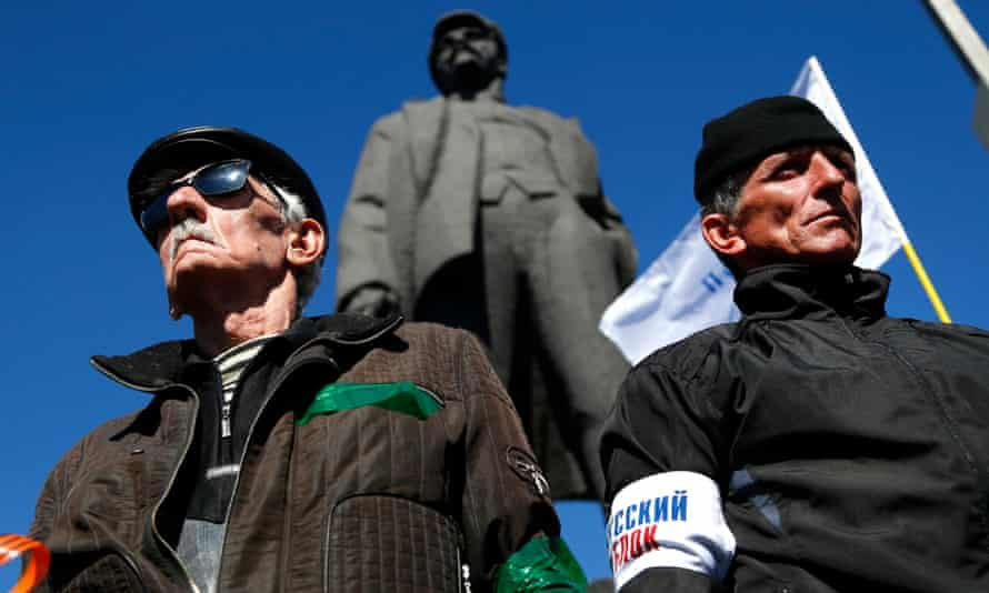 Pro-Russian activists stand guard during a rally in Donetsk, under a statue of Lenin. Ukraine