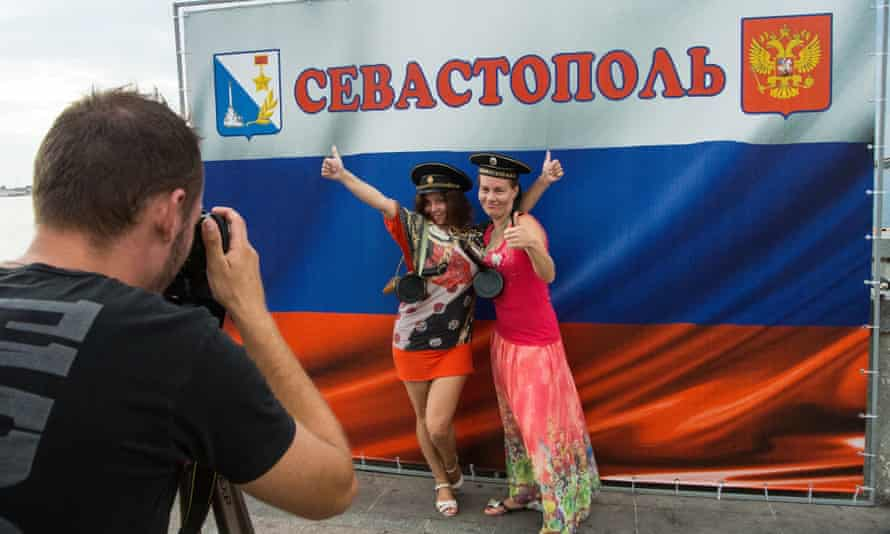 Women in Crimea pose for a picture next to a Russian flag with the word Sevastopol written on it. Ukraine