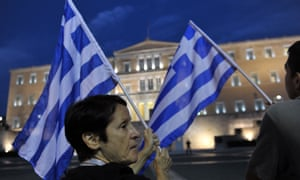 A protester holds a greek flag in front of the Greek parliament during an anti-austerity demonstration in Athens.
