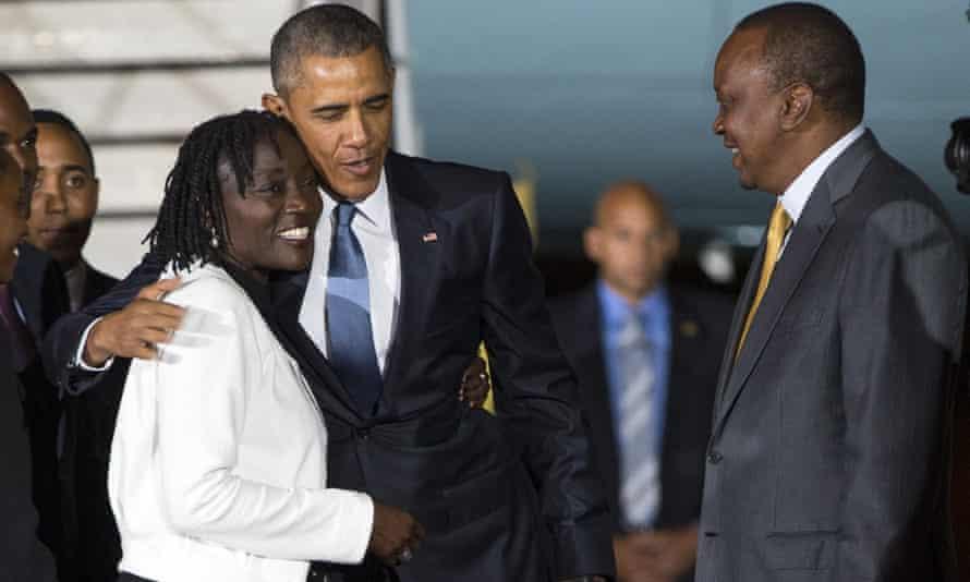 Kenyan president Uhuru Kenyatta, watches as Barack Obama hugs his half-sister, Auma Obama, after arriving in Nairobi.
