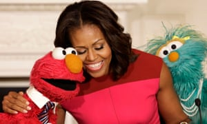 Michelle Obama hugs PBS Sesame Street characters Elmo and Rosita