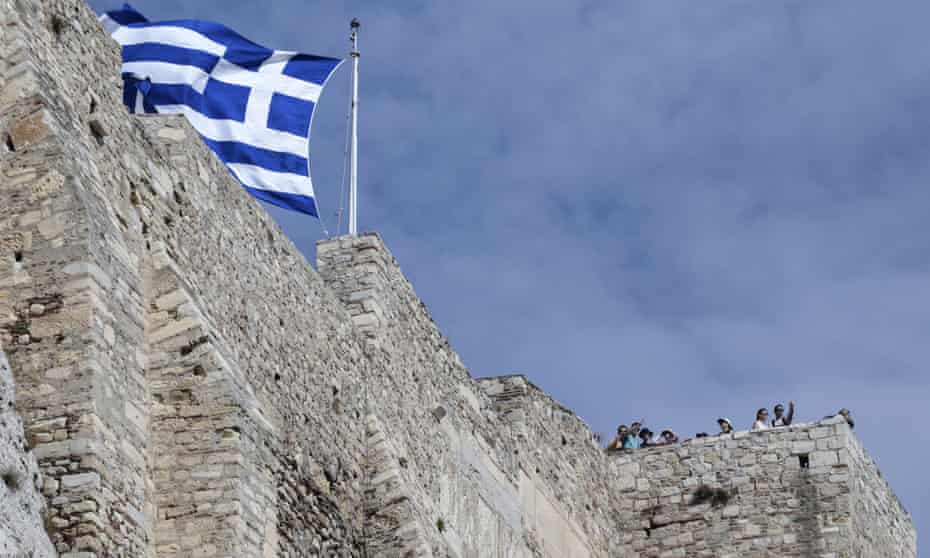 The Greek flag flies on the Acropolis hill in Athens.