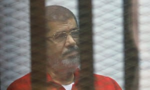 Mohamed Morsi sits in the defendants' cage during his trial