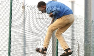 A man climbing over a fence on to the tracks near the Eurotunnel site at Coquelles in Calais, France.