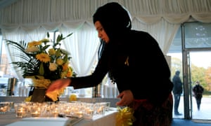 A woman lights a candle at the British Muslim Heritage Centre in Manchester before the start of memorial service for the murdered British hostage, Alan Henning.