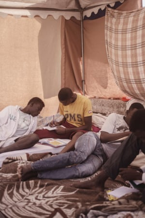 A group of men read as they bide their time